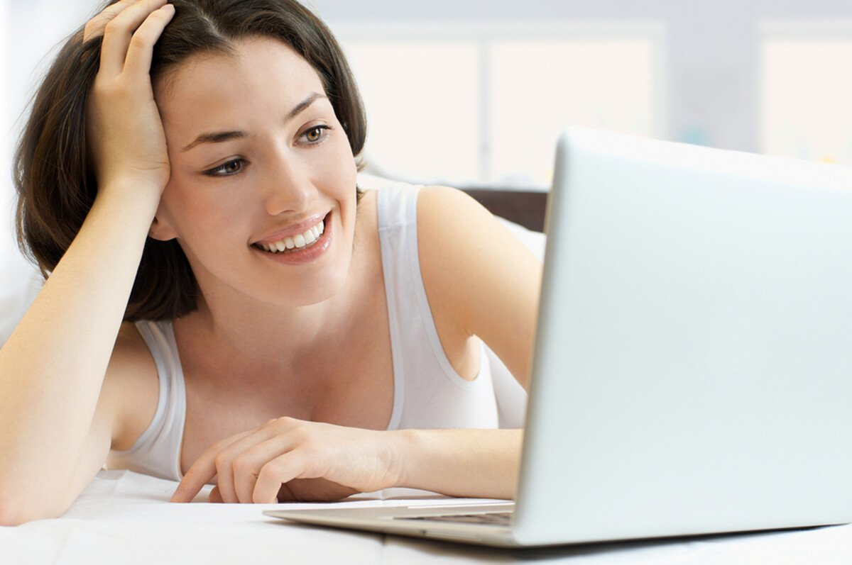 Woman looking at a laptop smiling