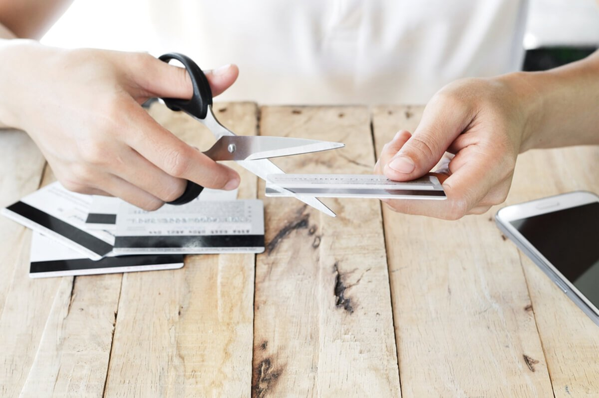 Person cutting up credit cards with scissors