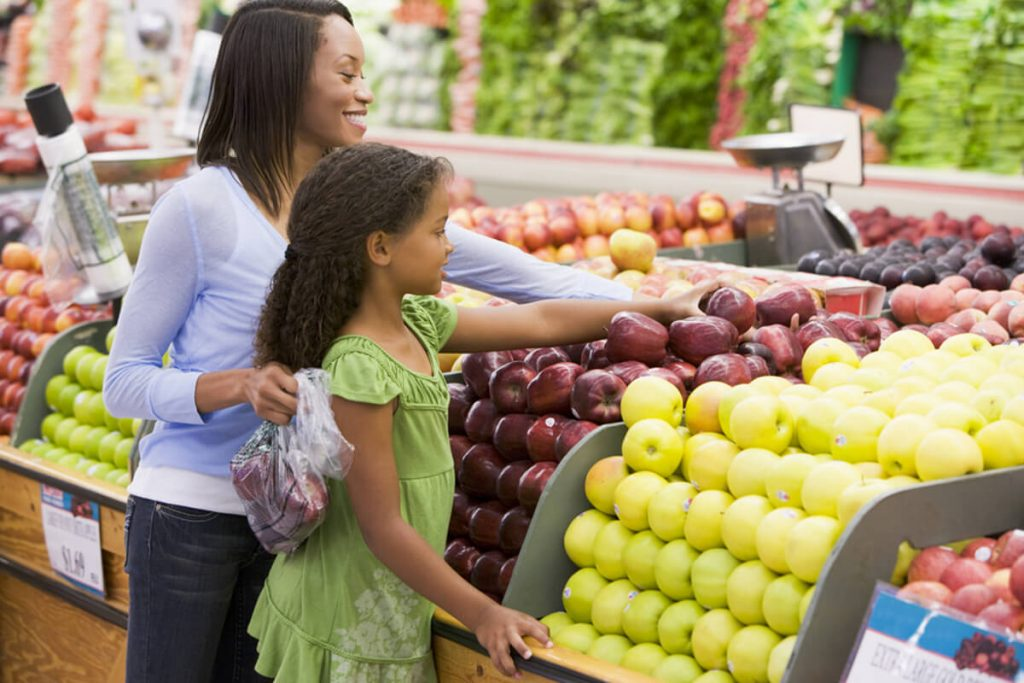 A woman and child shopping in a grocery store