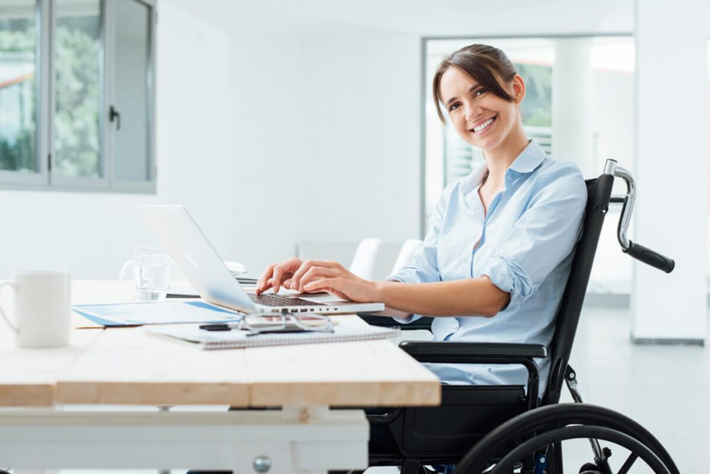 Woman in a wheel chair working on a laptop