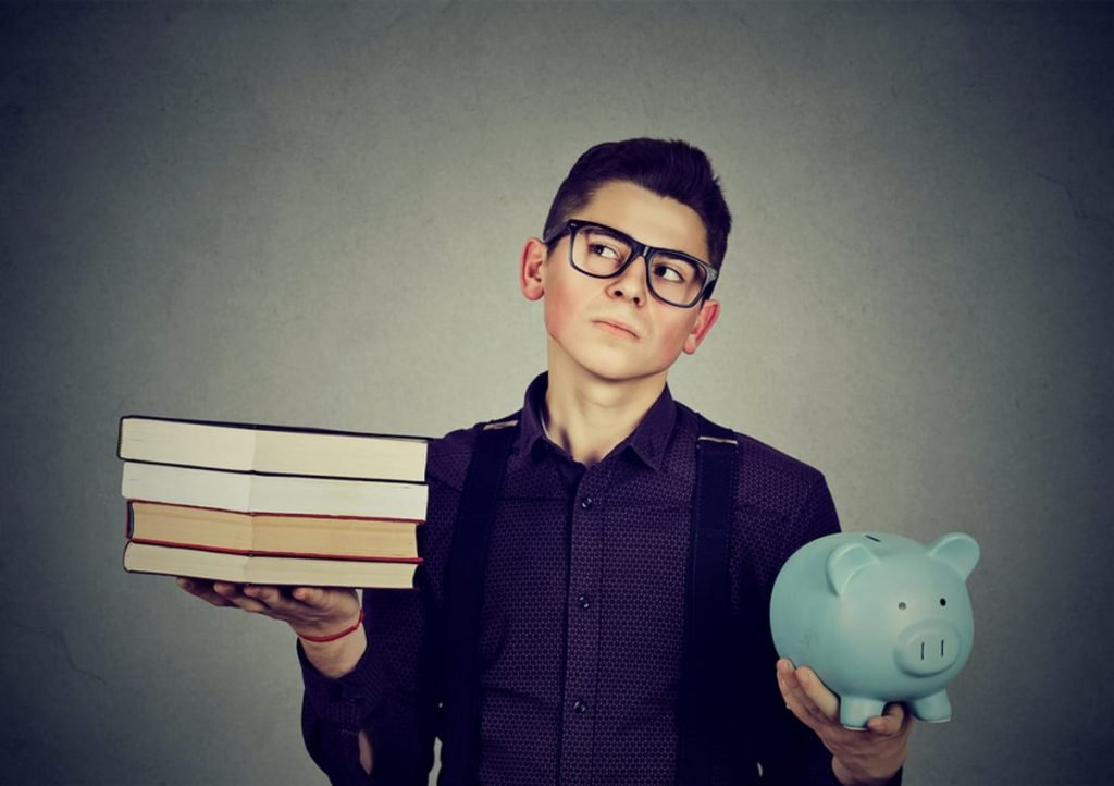 Young man holding a piggy bank in one hand and books in the other