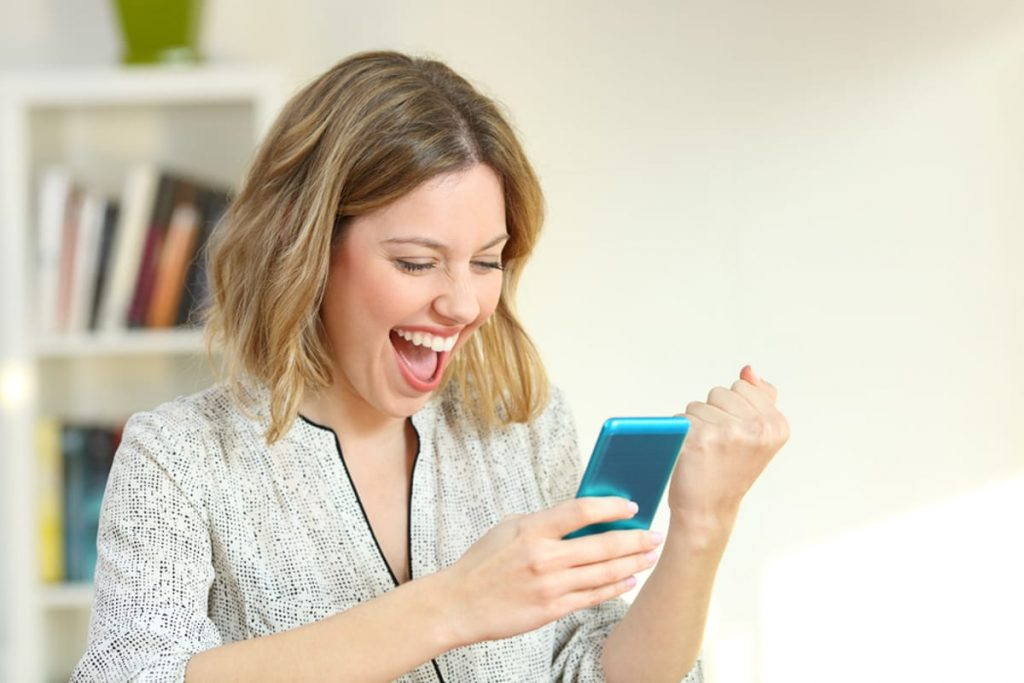 Woman looking at her mobile phone looking very excited.