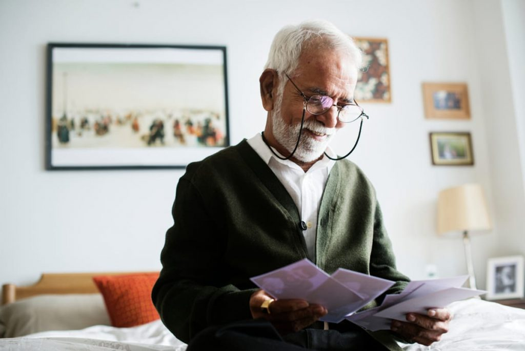 Elderly man with glasses reading letters.