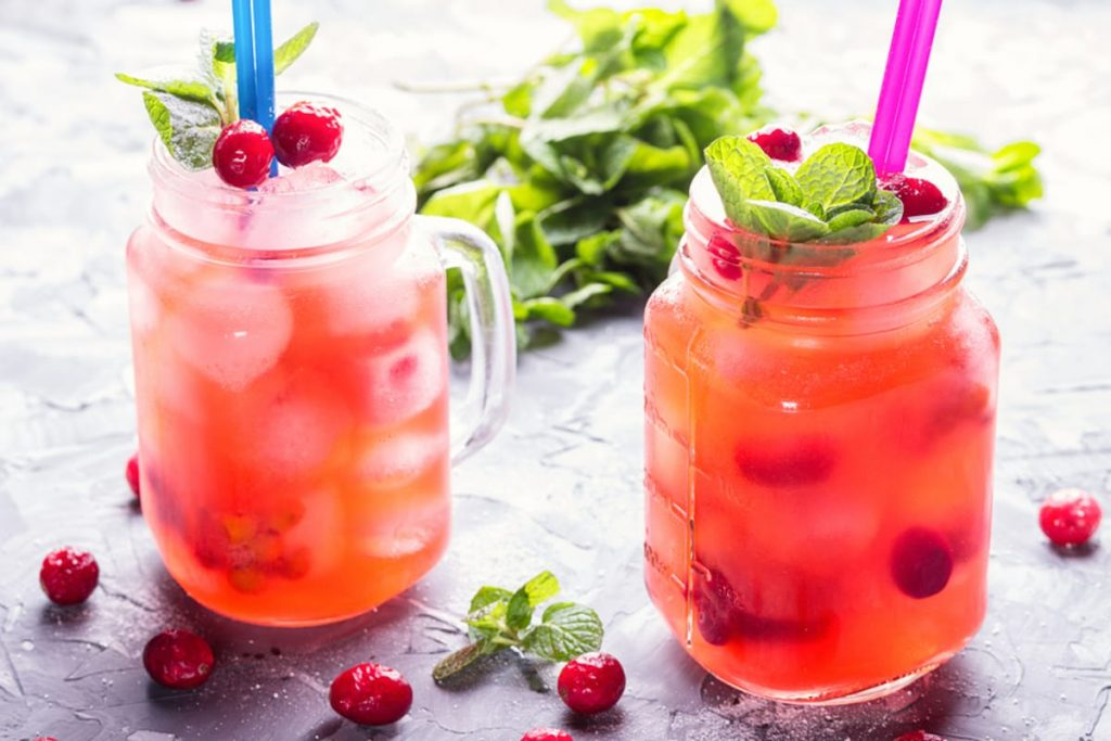 Two pink drinks in mason jars with cranberries around them.