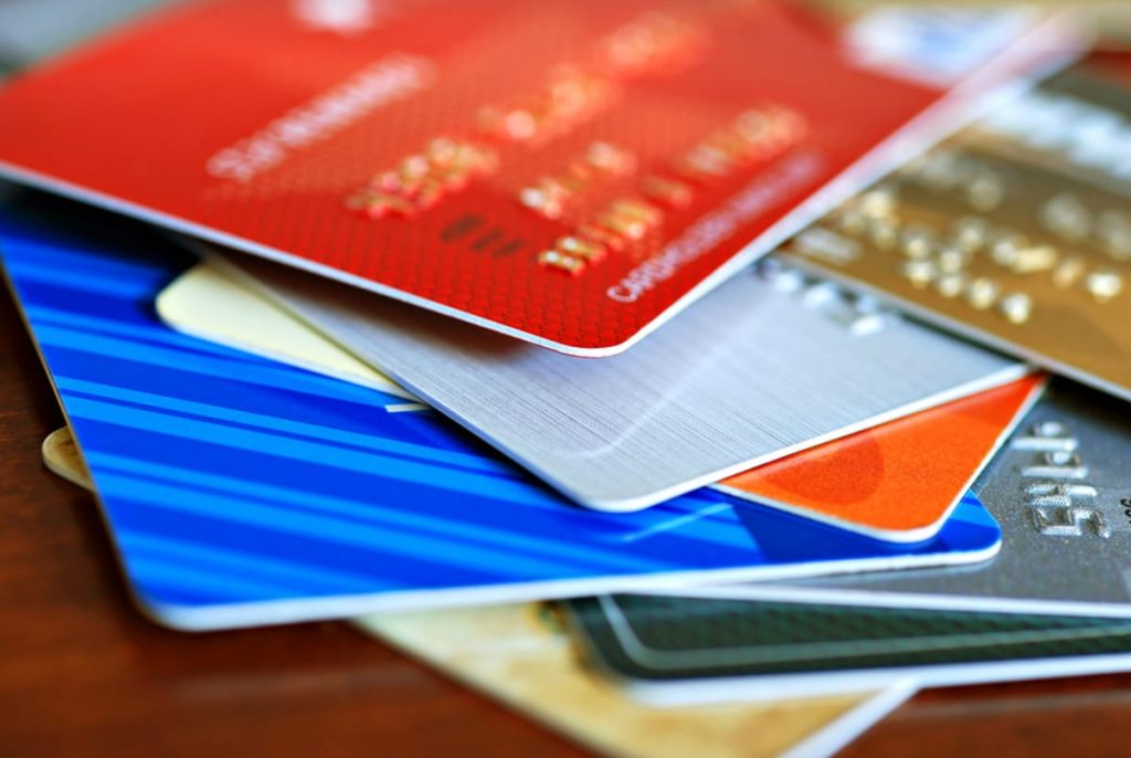 Multiple credit cards in a pile on a table.