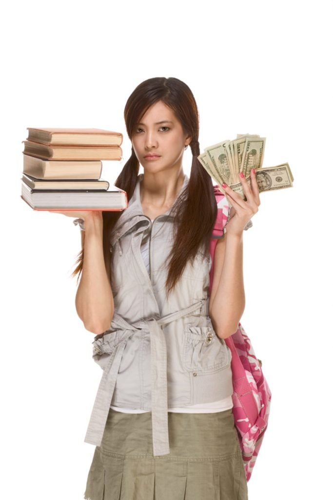 Young woman holding a stack of books in one hand and cash in the other.