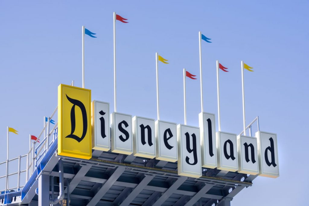 Classic Disneyland sign with flags on the top.