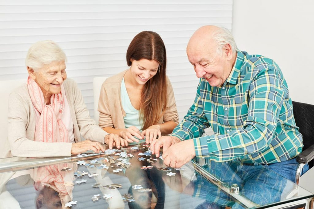 An elderly couple working on a puzzle with an adult daughter.