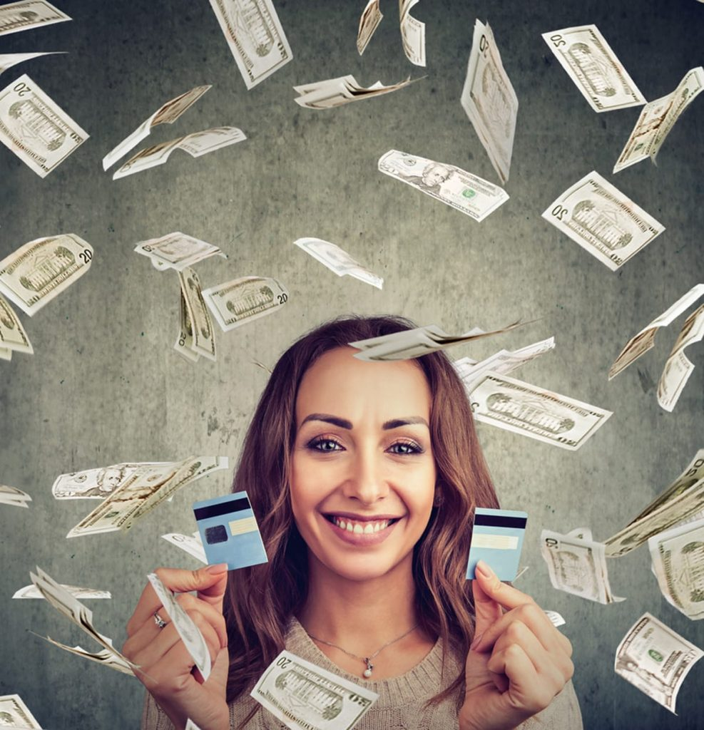 Woman smiling with money falling around her and a credit card cut in half.