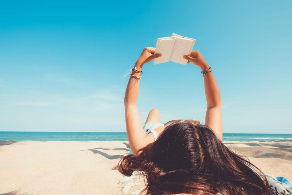 Woman lying on the beach reading a book.
