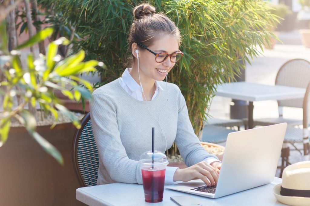 Woman working outside on a laptop.