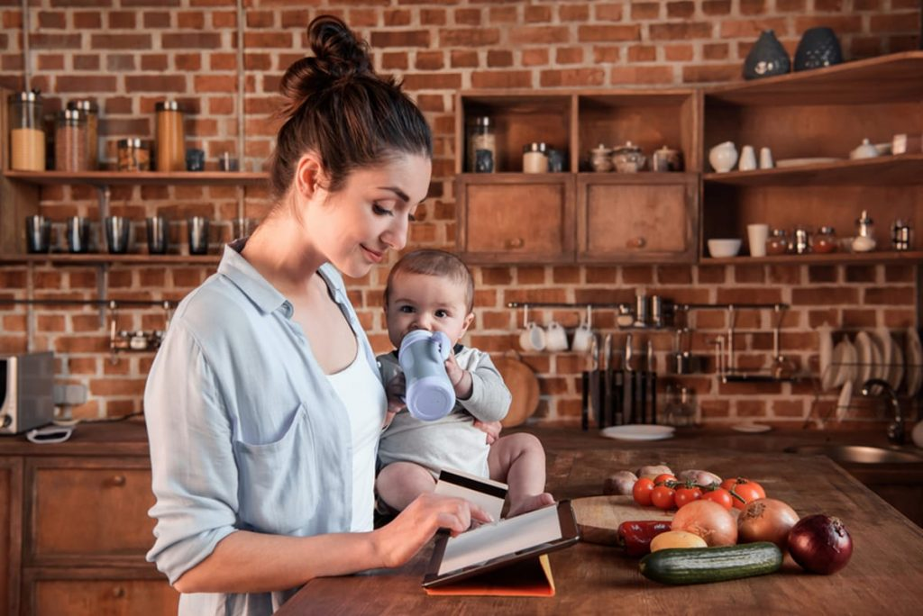 Mother with baby on counter looking at tablet.