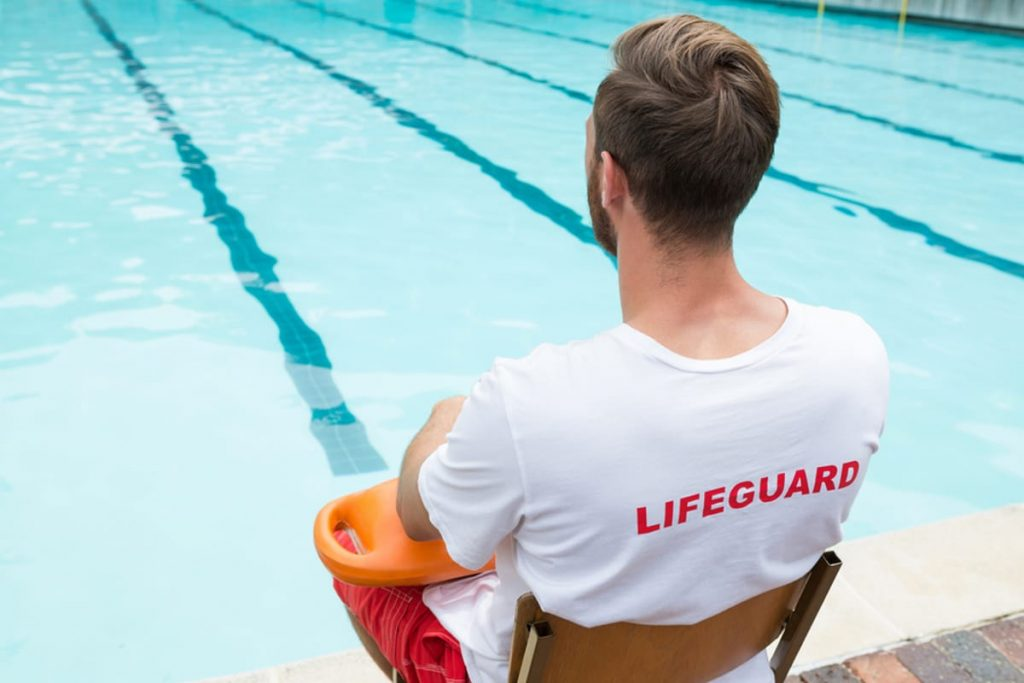 Lifeguard sitting with an inflatable looking out a pool.