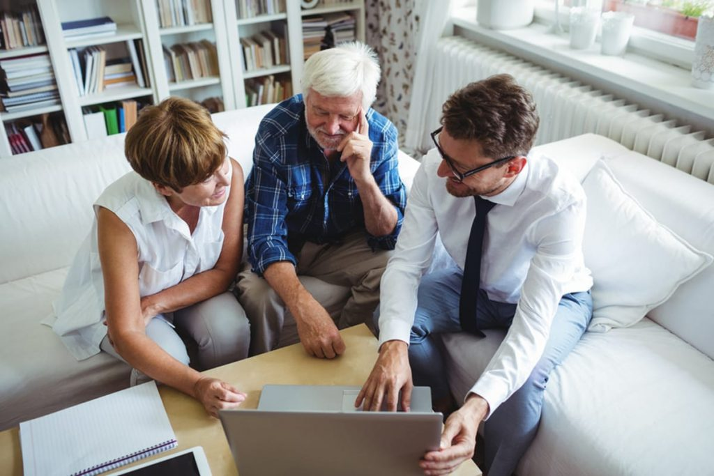 Elderly couple meeting with a young investment counselor.
