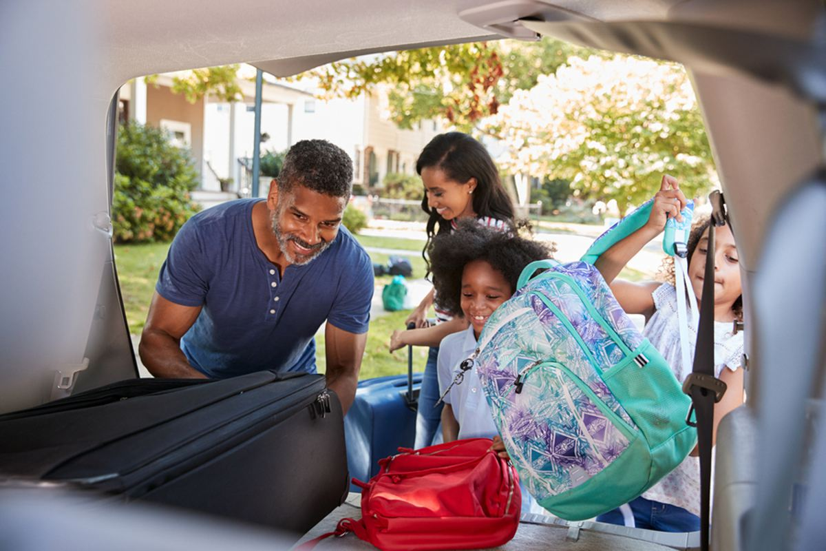 cheap vacation ideas -Family packing their car with suitcases.