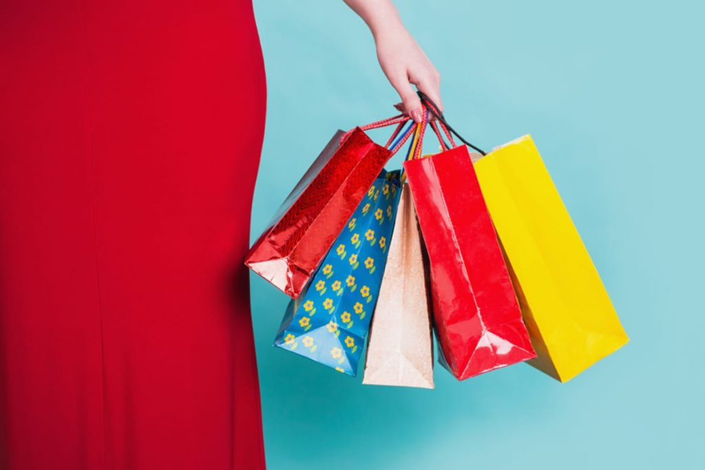 Woman with a red skirt holding shopping bags.