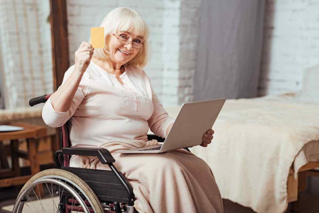 Woman in a wheelchair with her laptop and a medical credit card.