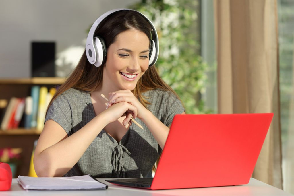 Woman wearing headphones smiling in front of a laptop computer.