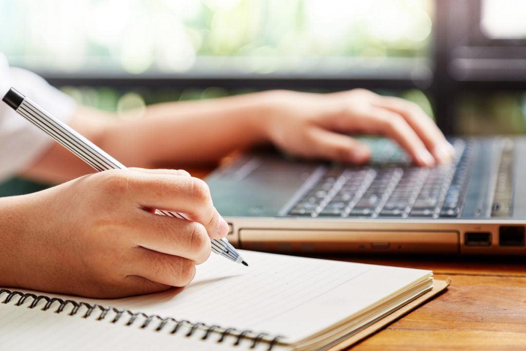 person typing on a laptop computer and writing notes on a pad of paper.