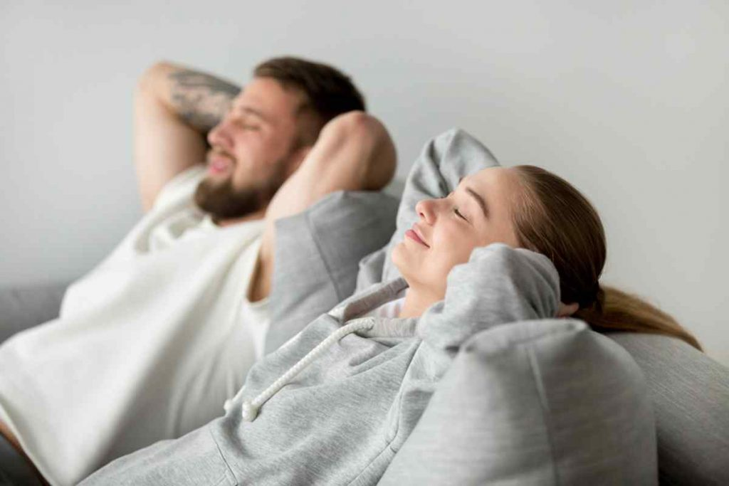 Couple lounging on a couch with their eyes closed appearing relaxed.