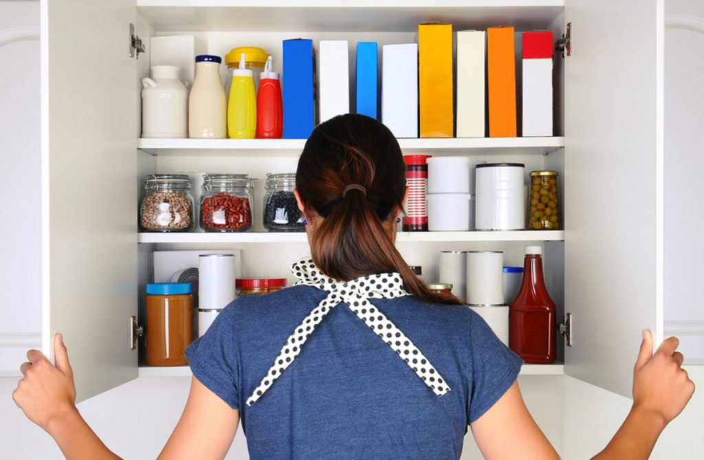 Woman opening a kitchen cabinet filled with food items.