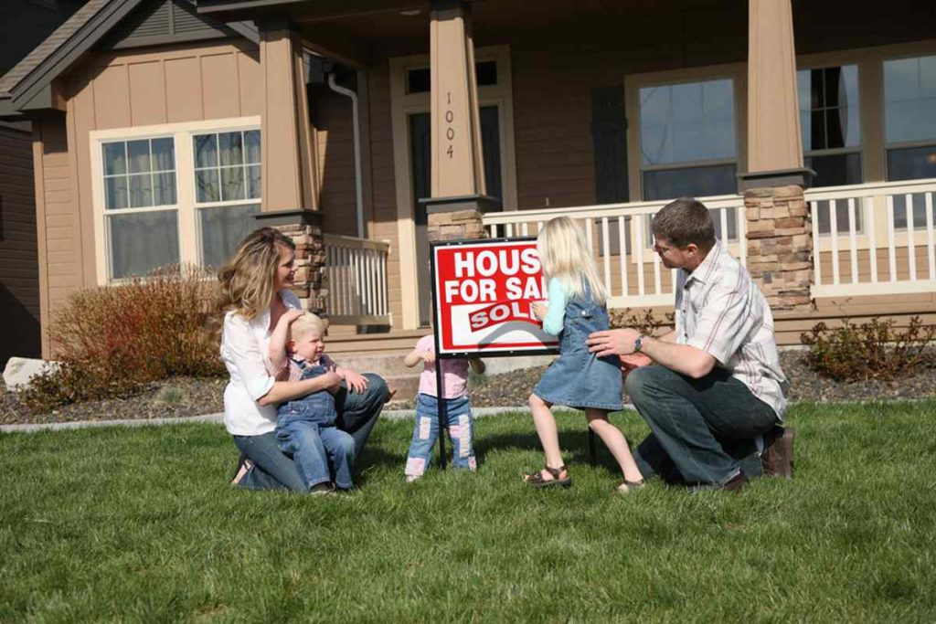 Family outside in front of home around a House for Sale sign.