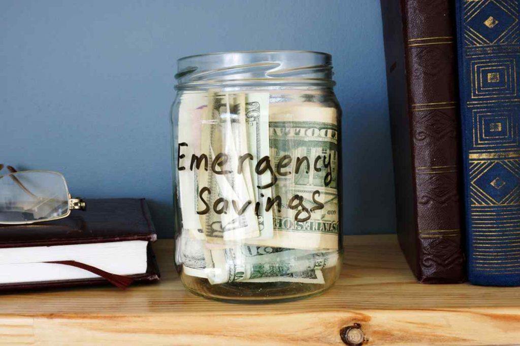Glass jar with emergency savings written on the side.