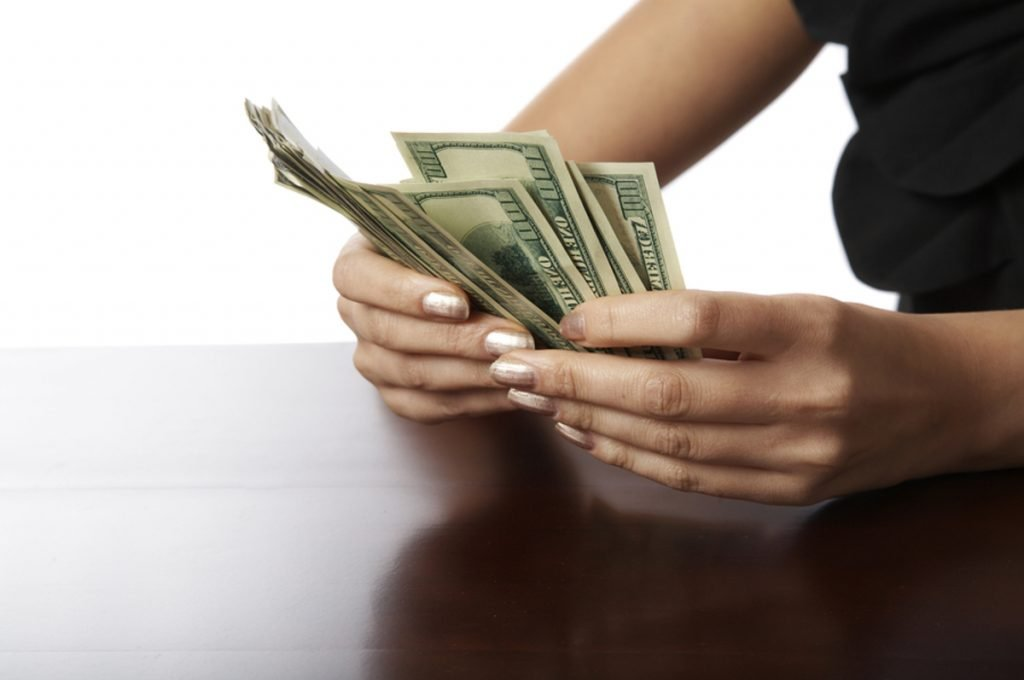 Woman counting one hundred dollar bills.