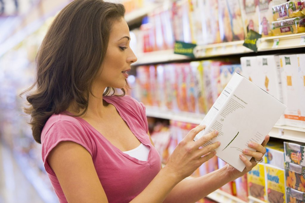 Woman reading a label in a grocery store.