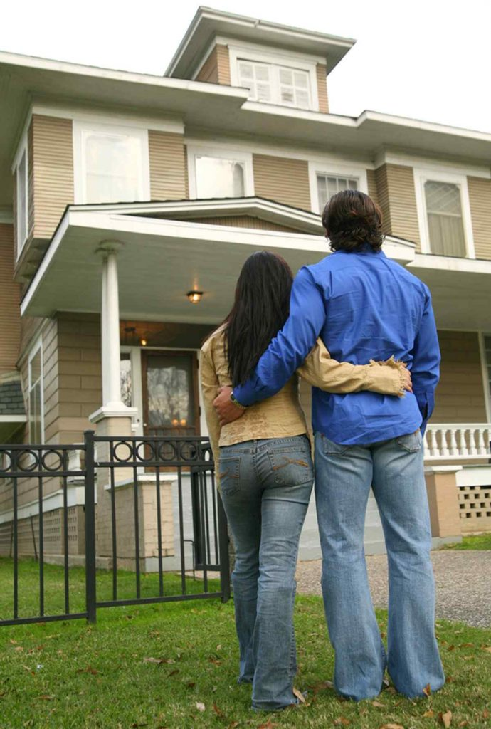 Couple with their arms around each other looking at a home.