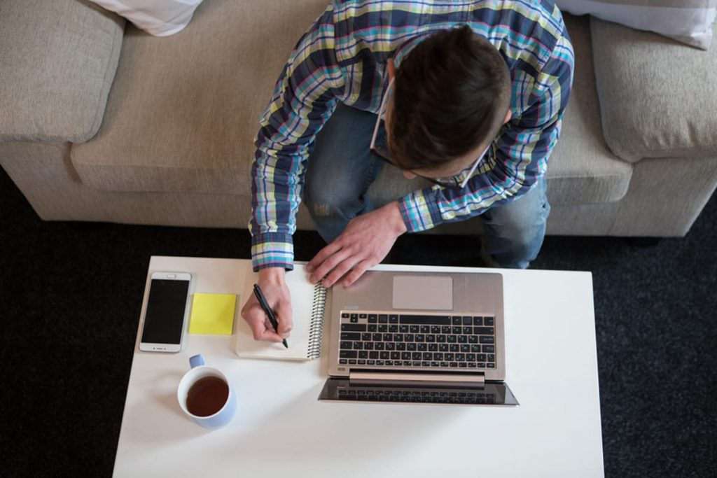 Man sitting on a couch working at a coffee table with his laptop.