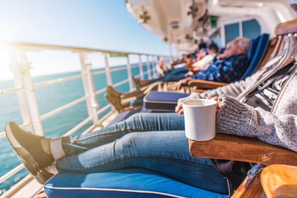 Row of people lounging on a cruise ship.