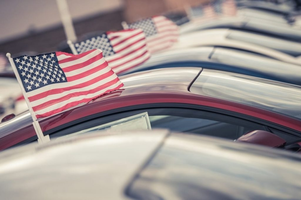 Row of cars with American flags at a car sales lot.