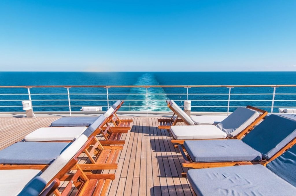 Cruise boat with lounge chairs on the rear deck.