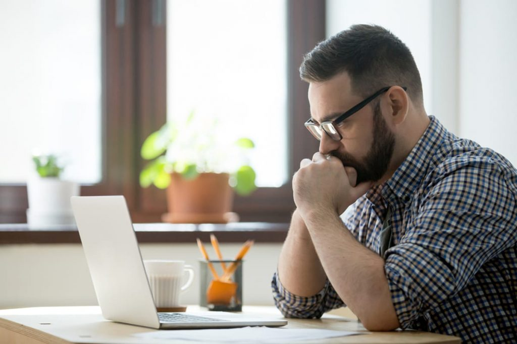 Man sitting at a table looking intently at his laptop.