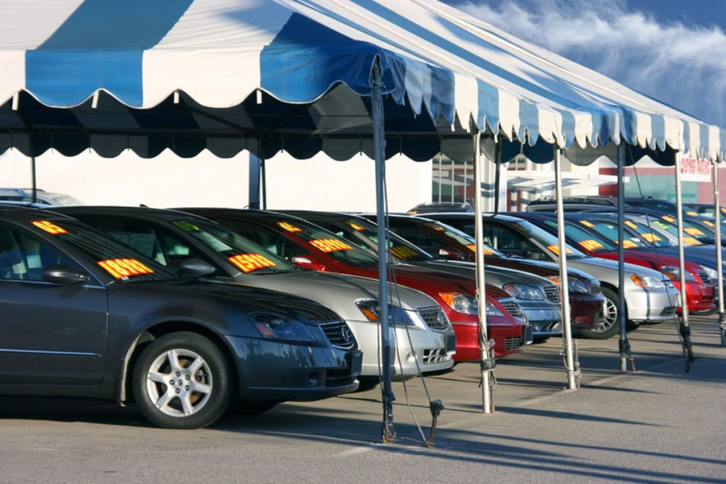 Row of cars under a tent at a car sales lot.