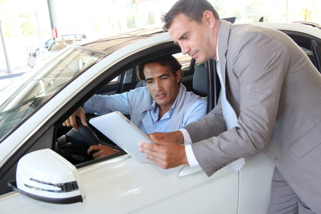Man sitting in a new car at a dealership speaking with a salesman.