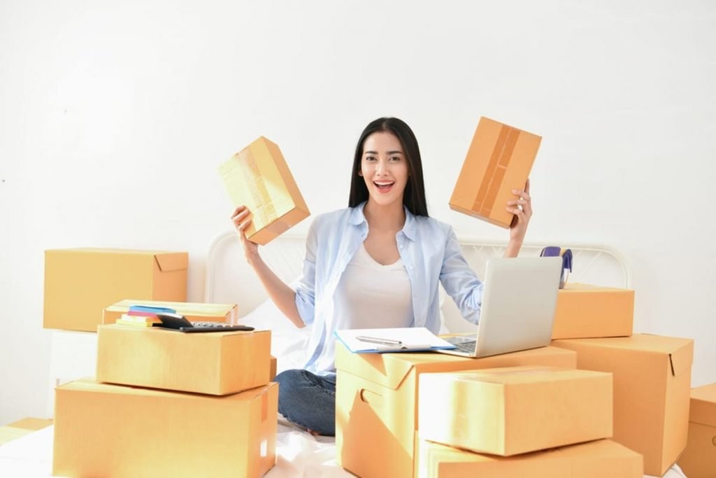 Woman surrounded by packed cardboard boxes.
