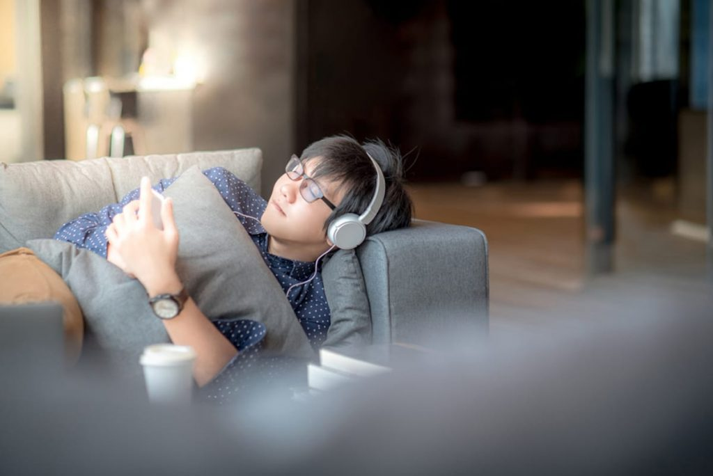Man lying down on a couch with headphones on sleeping.