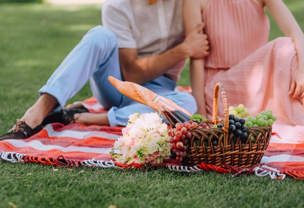 Couple sitting on a blanket having a picnic.