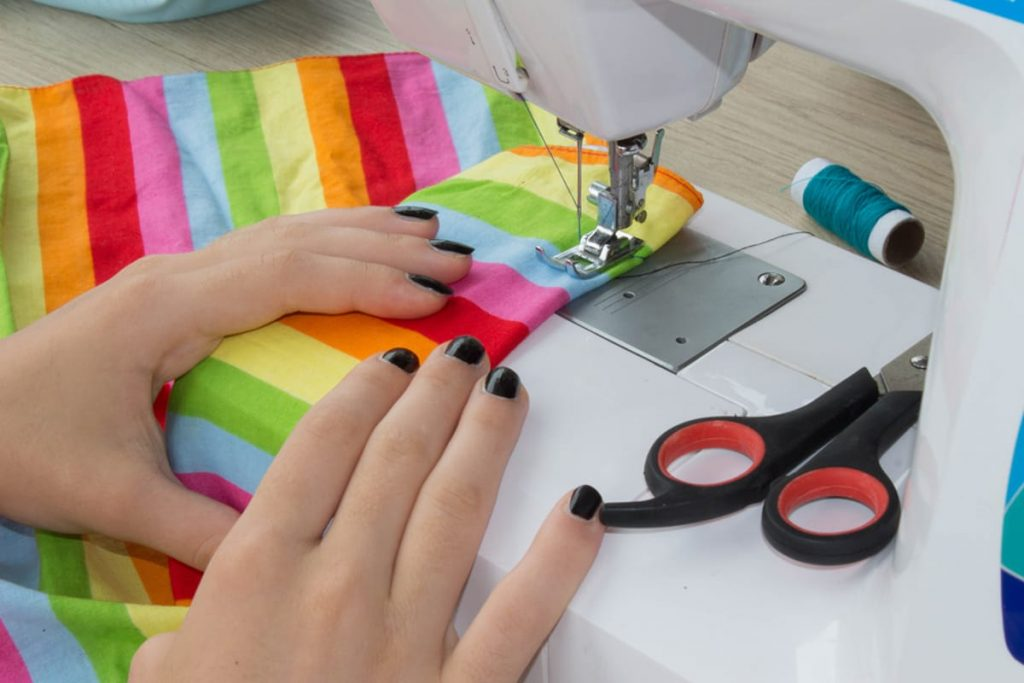 Person sewing rainbow colored material on a sewing machine.