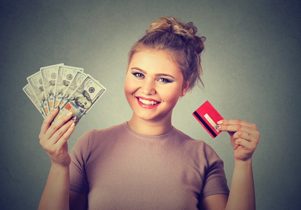 Woman with a fan of paper money and a credit card smiling.