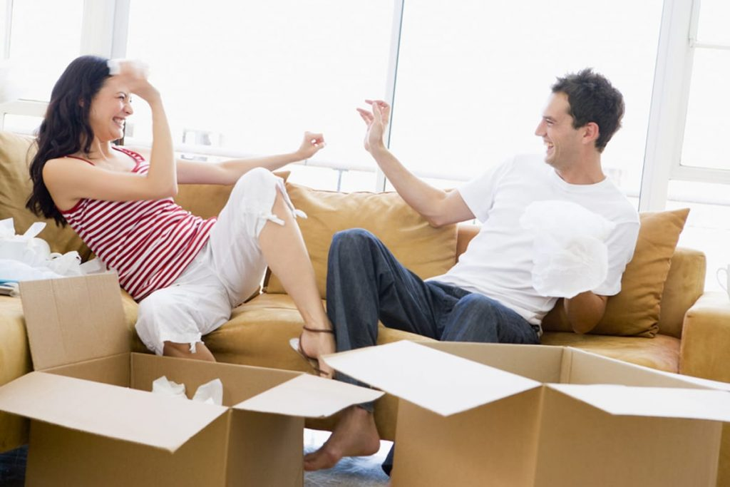 Couple sitting on a couch with cardboard boxes nearby.