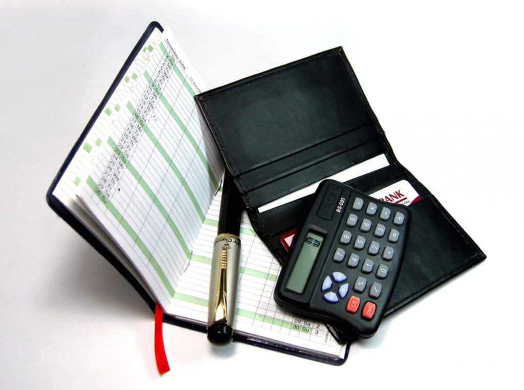 Calculator, ledger and wallet on a table top.