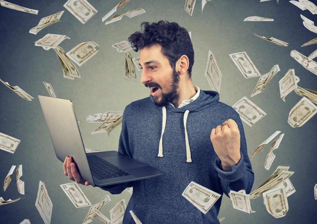 Man looking at his laptop with an excited expression and paper money falling down around him.
