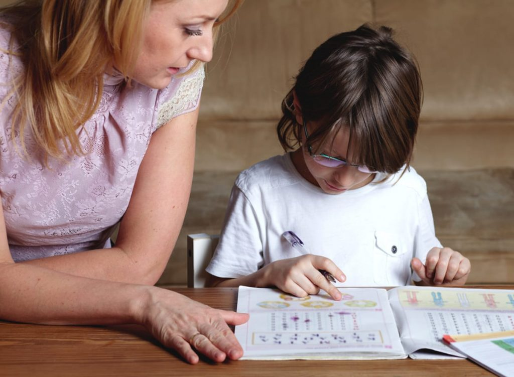 Woman helping a child with homework.